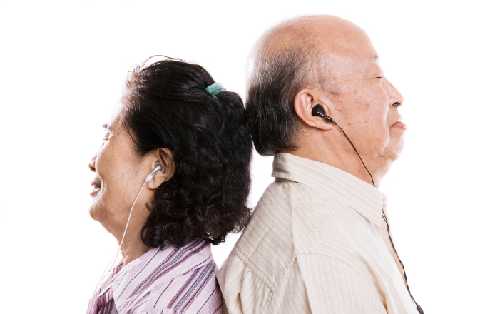 An isolated shot of a senior asian couple listening to music